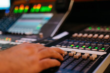 Sound Engineer's Hand On Mixer Board