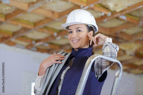 Fototapeta female constructor measuring the power-pipe for renovation obraz