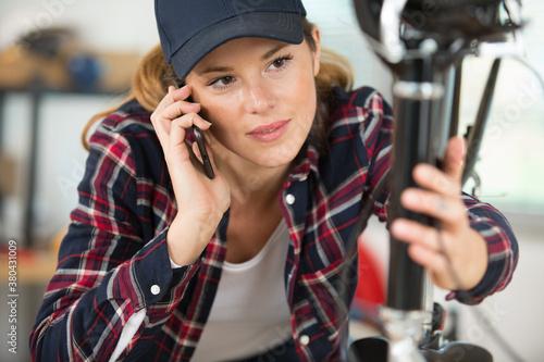 Fototapeta female mechanic studying bicycle frame and talking on telephone obraz