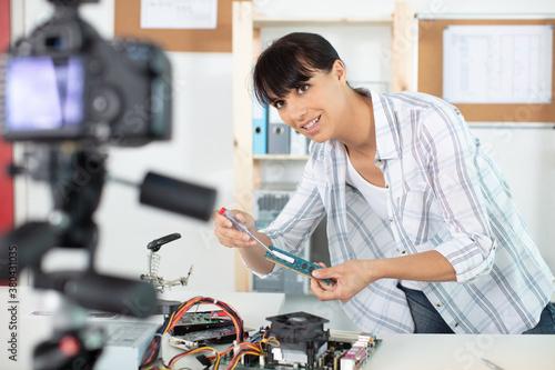 Fototapeta female vlogger recording computer repair on camera for vlog blog obraz