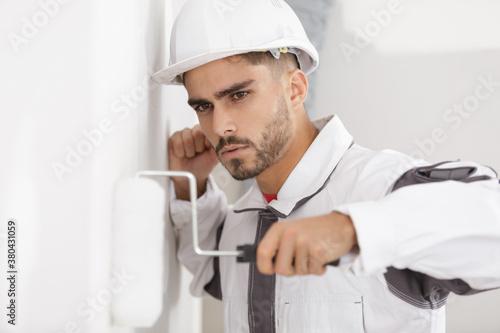 Fototapeta man constructor in helmet plastering wall with rolle obraz