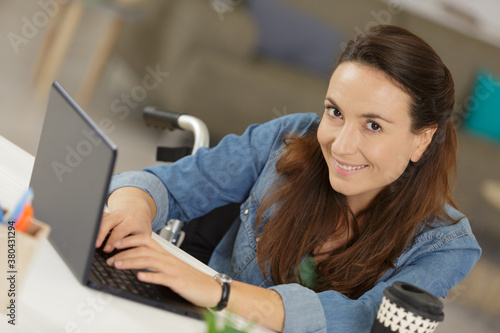 Fototapeta happy disabled woman in wheelchair with laptop obraz