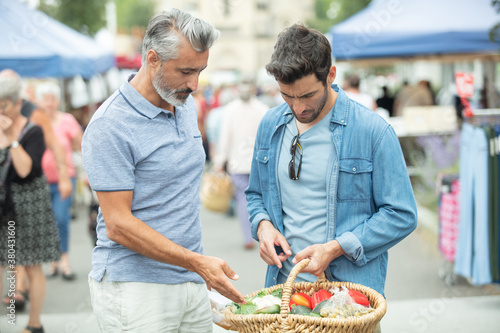 Fototapeta father and son buying vegetable at market obraz