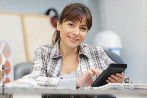 Fototapeta woman using a calculator in the office obraz