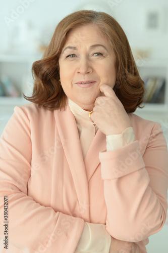 Happy mature woman in pink jacket posing at home Tapéta, Fotótapéta