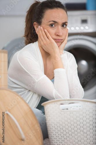 Fototapeta upset woman sitting at laundry room besides empty basket obraz