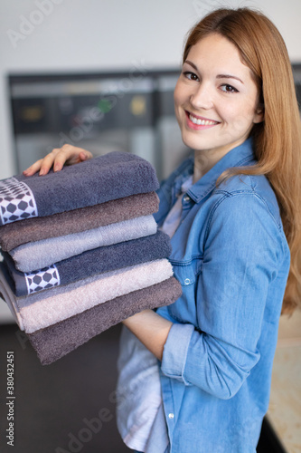 Fototapeta beautiful young woman smiling after ironing clothes at home obraz