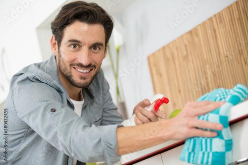 Fototapeta guy cleaning glass in living room obraz