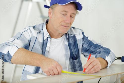 Fototapeta mature builder taking measures indoors obraz