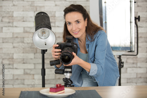Fototapeta female food photographer taking picture of tasty cake in studio obraz