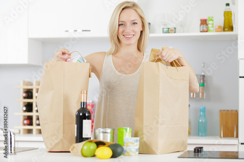Fototapeta woman attractive housewife in kitchen with grocery shopping bag obraz