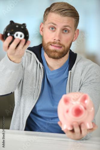 Fototapeta man sitting with a piggy bank obraz