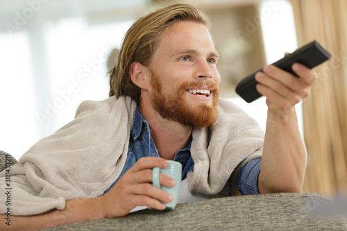 Fototapeta happy young man with tv remote control on sofa obraz