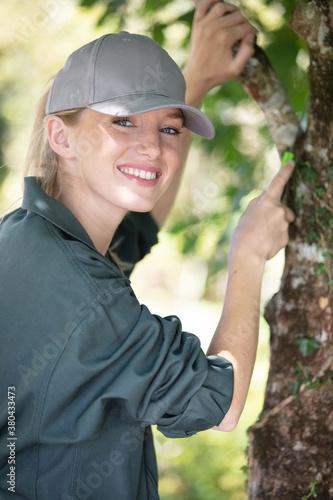 Fototapeta young woman gardener smiling with tree obraz
