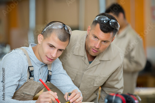 Fototapeta young apprentice with teacher working with wood obraz