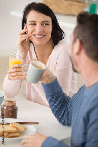Fototapeta couple with breakfast on tray at home in the kitchen obraz