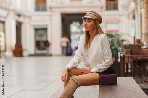 Fototapeta Blond sexy european woman in trendy autun cap posing outdoor. Wearing white blouse and leather skrt and knitted block  thigh high boots in beige. obraz