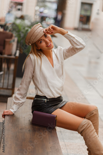 Obraz Blond smiling european woman in trendy autunb cap posing outdoor. Wearing white blouse and leather skrt and knitted block  thigh high boots in beige. - fototapety do salonu