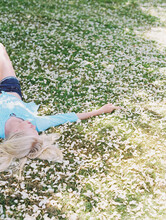 Blonde Girl On Green Grass With White Flower Petals And Sunlight On Film