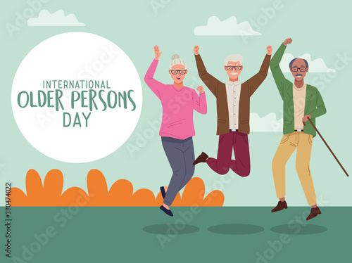 Fototapeta international older persons day lettering with old people jumping celebrating in the field obraz