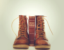 Bible And Boots On Gray Background