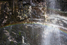 Waterfall Coming Down A Dark Rocky Cliff, With Rainbow
