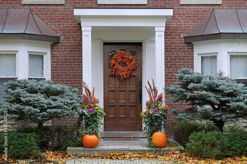 Fototapeta Front door with colorful fall wreath and pumpkins