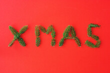 The Word XMAS, Formed By Little Pine Branches On Red Paper