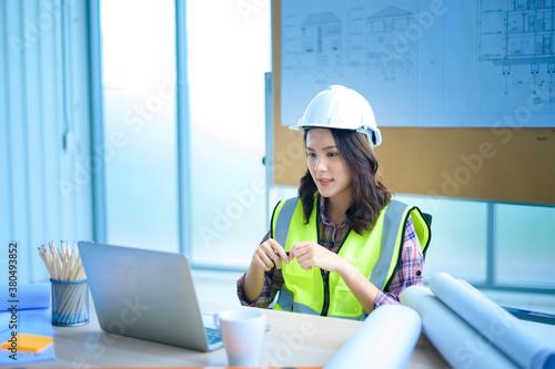 Fototapeta female engineer using laptop, making video call to client or business partner obraz