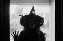 A Woman Dressed As A Witch At The Front Door