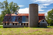 An Abandoned Old Farm House With A Tall Brick Silo And A Big Barn With Rusted Tin Ceiling. This Very Old Run Down Builsing Complex Is Surrounded By Grassland And Trees. Image Taken In Rural Maryland.