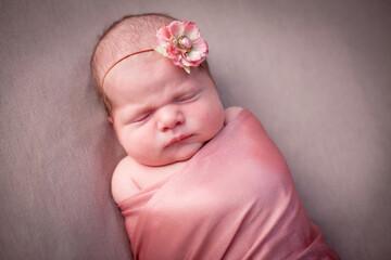 Newborn Baby Girl Sleeping Peacefully Swaddled in Pink Blanket, Wearing Flower Headband
