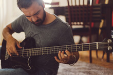 Man Playing Bass Guitar Sitting On The Floor