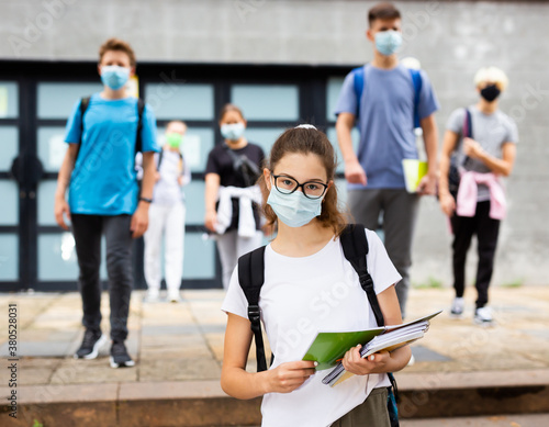 Portrait of teen girl student in face mask on her way to college in warm autumn day Fotobehang