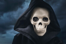 Close-up Of A Hooded Human Skeleton Against A Stormy Sky