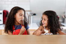 Cute Sisters Laughing Together While Eating Ice Cream Bars