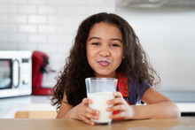 Funny Little Girl With Milk Mustache After Drinking Glass Of Milk