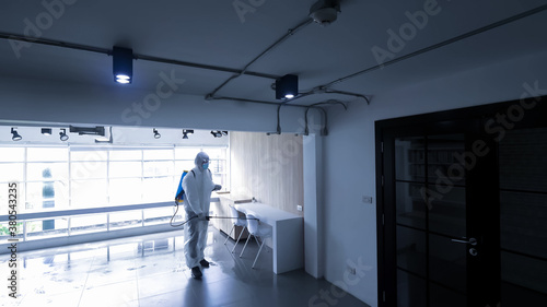 Fototapeta Worker in personal protective equipment (ppe) suit cleaning in building with spray disinfectant water to remove covid 19 obraz
