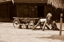 A Sepia Photo Of An Old Wooden Horse Drawn Carriage On Wooden Wheels With An Imitation Of A Horse Or A Pony Made Out Of Logs, Planks And Boards Seen On A Polish Countryside In Summer