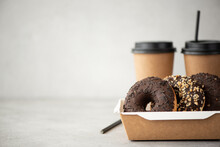 Chocolate Donuts With Glaze In A Craft Box And Black Coffee In Cups