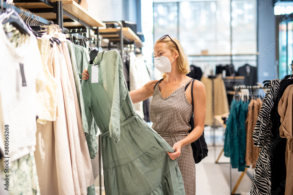 Fototapeta Fashionable woman wearing protective face mask shopping clothes in reopen retail shopping store. New normal lifestyle during corona virus pandemic.