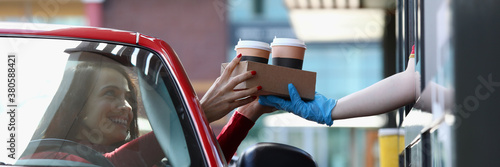 Fototapeta Woman in convertible car picks up tea and coffee in Mcdrive. Fast and safe service in restaurants and cafes concept obraz