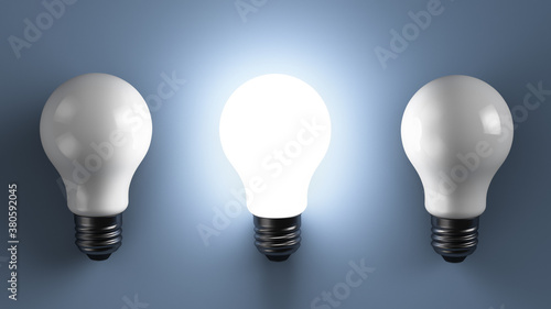 Three energy efficient lamps on the table. One of them shines. Slika na platnu
