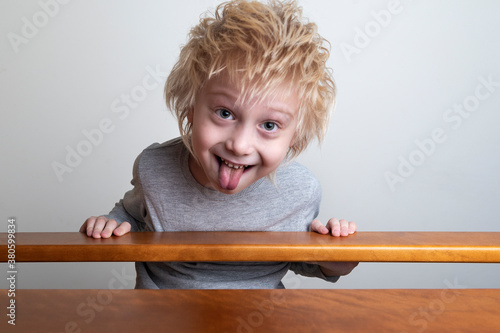 Cuadros en Lienzo Funny boy with blond hair leaned over the banister and looks down