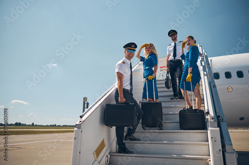 Canvas Print Beautiful female stewardesses with two handsome pilots looking and posing at the