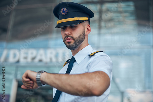 Handsome male pilot looking at wristwatch on the street Poster Mural XXL