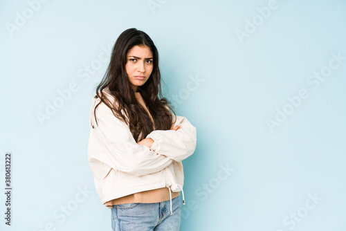 Young indian woman on blue background frowning face in displeasure, keeps arms folded Fototapet