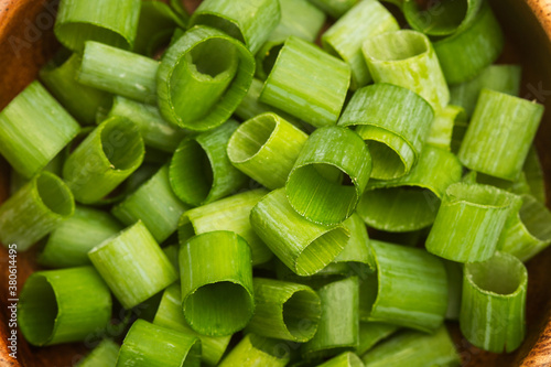 Fotografie, Obraz Cebolla verde cortanda en trozos pequeños dentro de un cuenco de madera