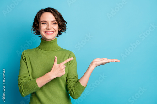 Fototapeta Portrait of positive cheerful girl hold hand point index finger copyspace recommend suggest select adverts promo wear stylish trendy pullover isolated over blue color background obraz