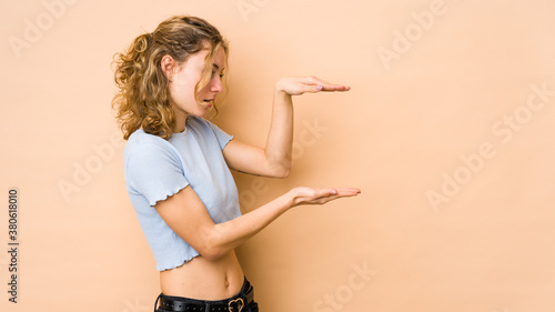 Young caucasian woman isolated on beige background shocked and amazed holding a copy space between hands Wallpaper Mural